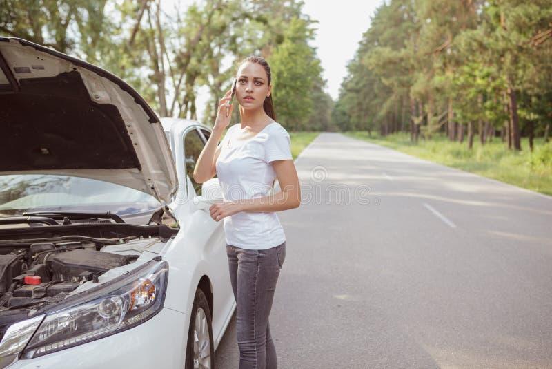 Jonge mooie vrouw met een gebroken auto op de weg stock foto