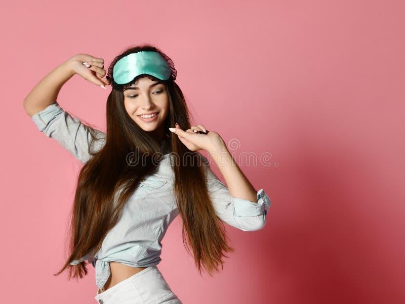 Jonge mooie vrouw met een masker voor slaap op een roze isolatie als achtergrond stock fotografie