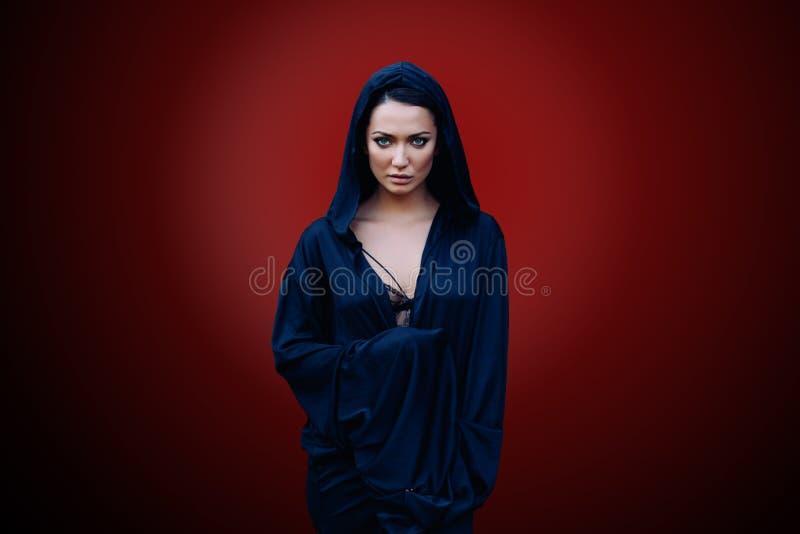 Jonge mooie vrouw met een zwart haar en in de donkerblauwe mantel met kap bij de rode achtergrond stock foto's