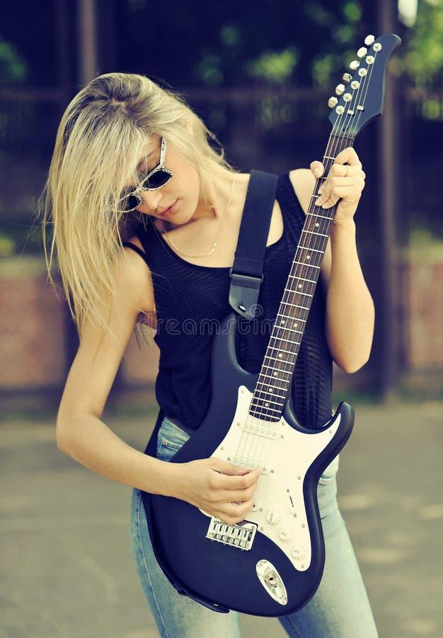 Jonge mooie vrouw met elektrische gitaar die zonnebril dragen stock afbeelding
