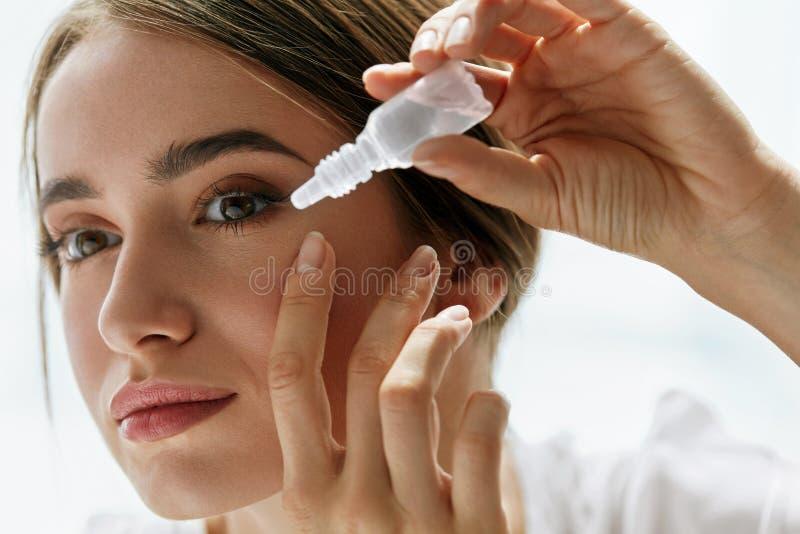 Jonge Mooie Vrouw met Eyedrops Visie en Geneeskundeconcept stock foto