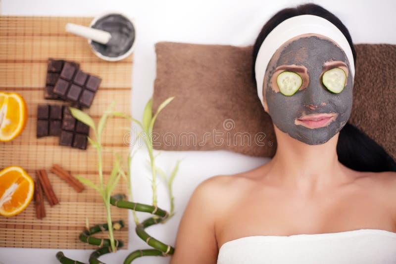 Jonge mooie vrouw met gezichtsmasker van komkommer op haar gezicht die bij kuuroordsalon liggen stock foto