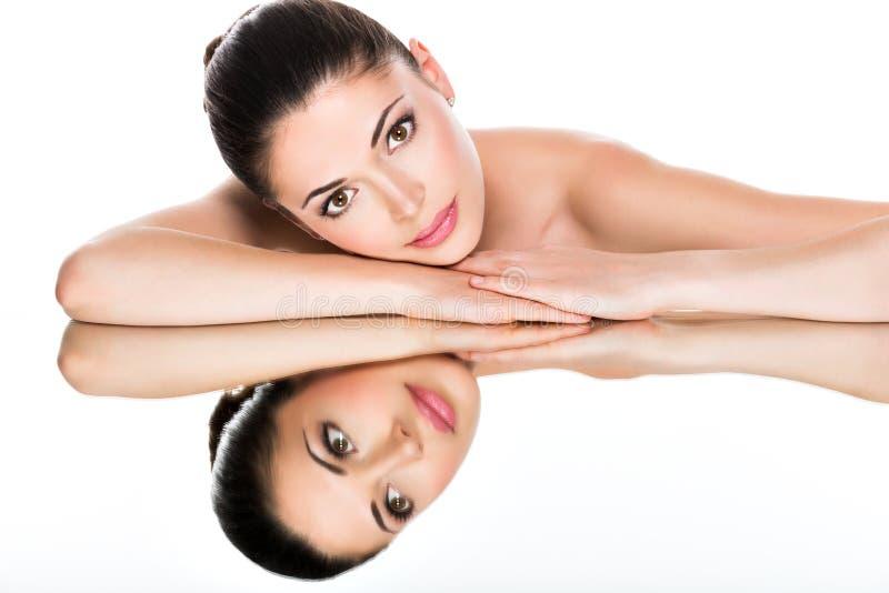 Jonge mooie vrouw met gezonde huidbezinningen in een spiegel stock afbeelding