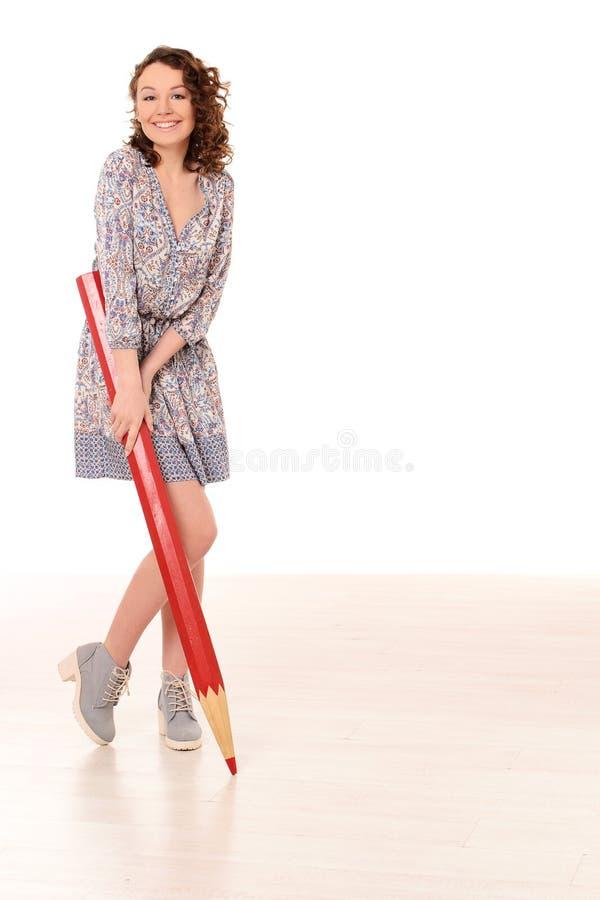 Jonge mooie vrouw met groot rood potlood royalty-vrije stock fotografie