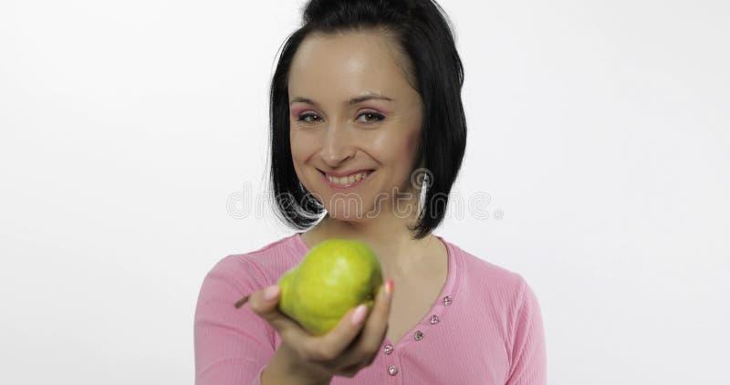 Jonge mooie vrouw met grote, verse, sappige, groene peer Aanbiedingsbeet aan kijker royalty-vrije stock foto