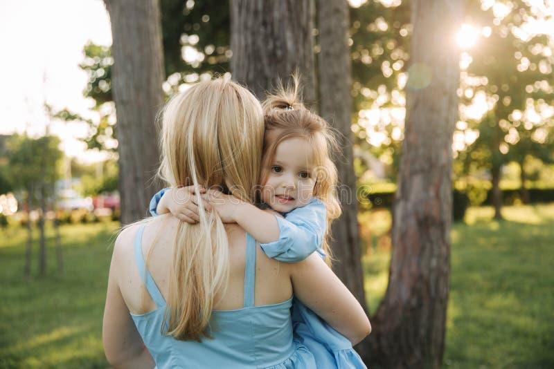 Jonge mooie vrouw met haar weinig leuke dochter De jonge dochter koestert moeder in de zomerpark stock foto's