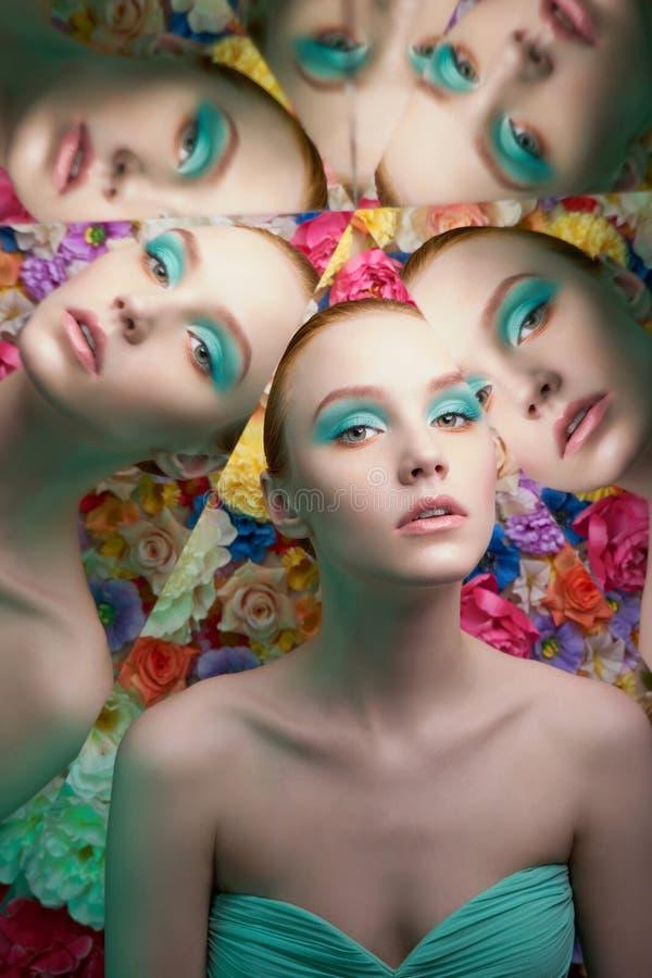Jonge mooie vrouw met heldere colorfullmake-up op bloemachtergrond stock foto's