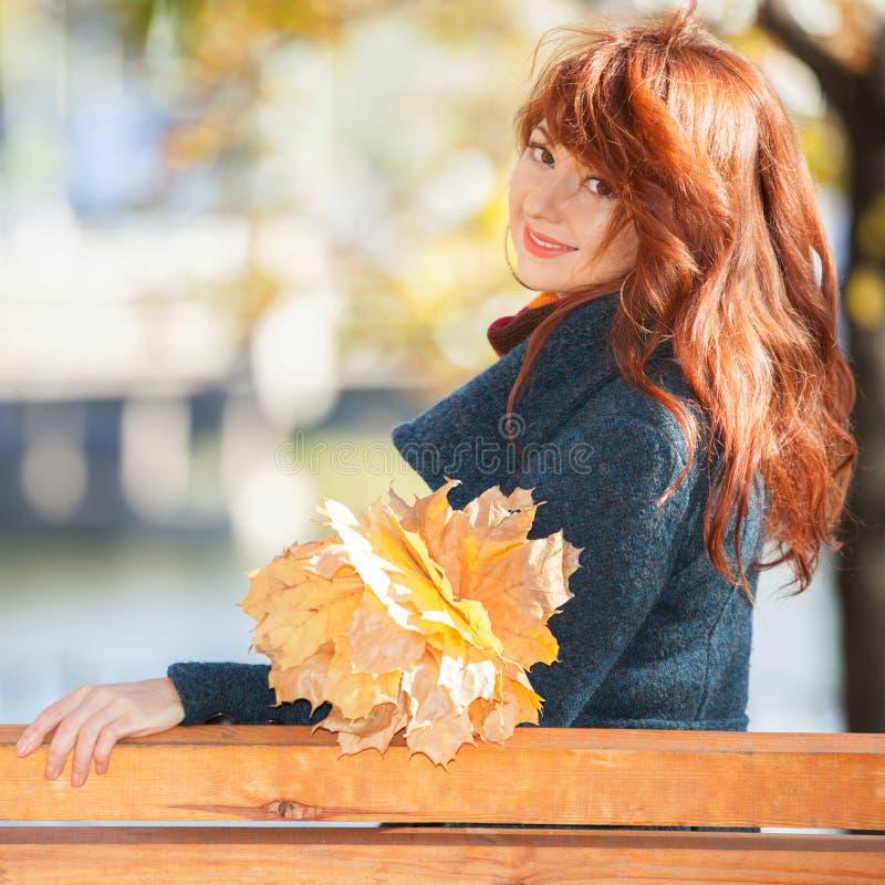 Jonge mooie vrouw met het rode haar ontspannen in het de herfstpark De sc?ne van de schoonheidsaard met kleurrijke gebladerteacht royalty-vrije stock afbeeldingen