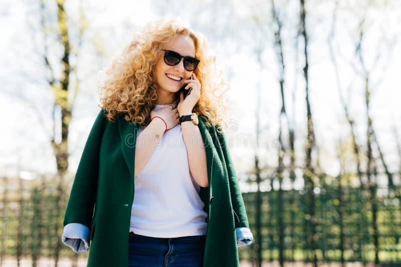 Jonge mooie vrouw met krullend blondehaar die zonnebril en groen jasje dragen die op haar cellphone spreken, die terwijl status g royalty-vrije stock foto's