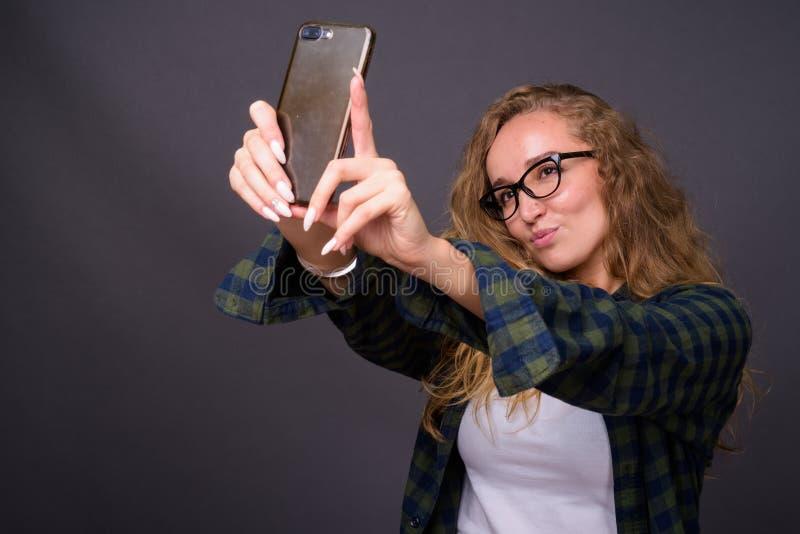 Jonge mooie vrouw met lang golvend blond haar die mobiele telefoon met behulp van royalty-vrije stock afbeeldingen