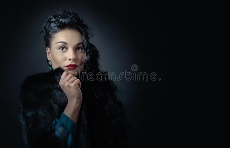 Jonge mooie vrouw met lang krullend haar in zwarte bontjas royalty-vrije stock fotografie