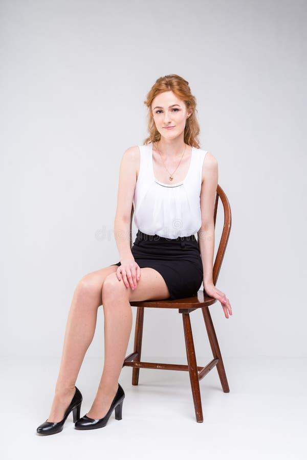 Jonge mooie vrouw met lange rode, krullende haarzitting op een houten stoel op een witte achtergrond in de studio Gekleed in een  royalty-vrije stock fotografie
