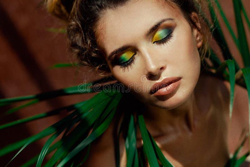 Jonge mooie vrouw met ogen die op tropische achtergrond worden gesloten stock fotografie