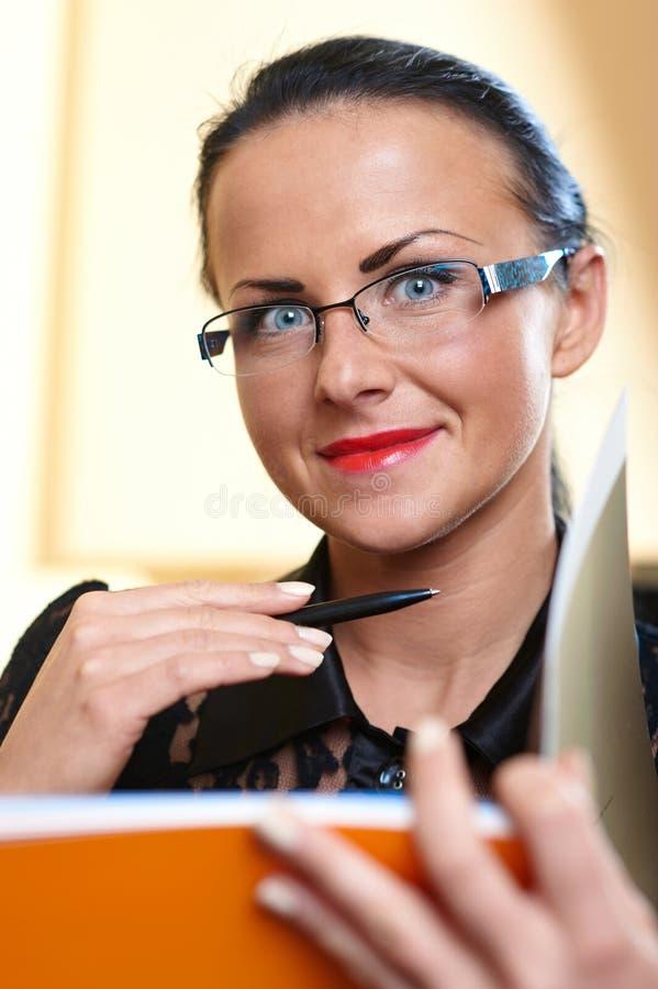 Jonge mooie vrouw met oranje boek in handen stock afbeeldingen