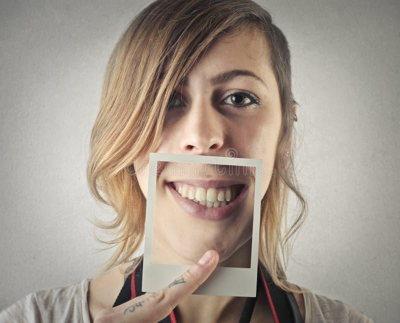 Jonge mooie vrouw met pic van haar glimlach stock fotografie
