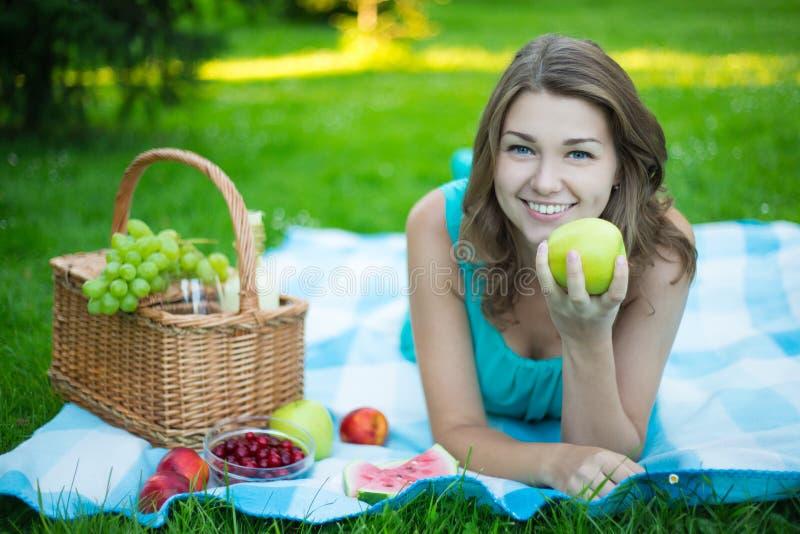 Jonge mooie vrouw met picknickmand en vruchten in tuin stock afbeelding