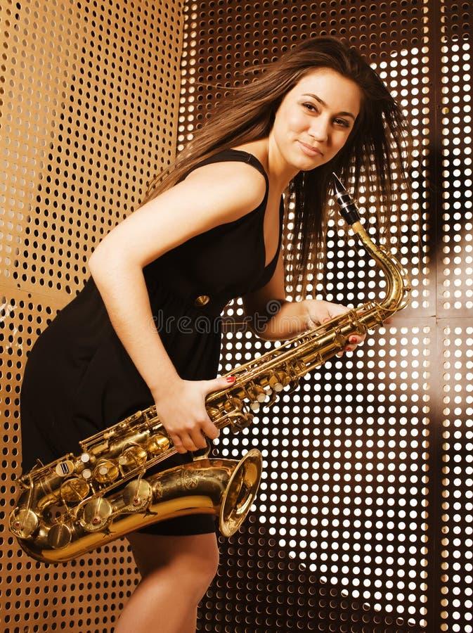 Jonge mooie vrouw met saxofoon stock afbeeldingen