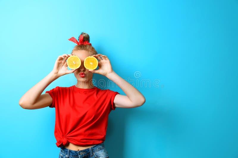 Jonge mooie vrouw met sinaasappelen op achtergrond stock fotografie