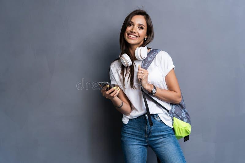 Jonge mooie vrouw met slimme telefoon Glimlachend studentenmeisje die op een reis gaan Ge?soleerdu op grijze achtergrond stock fotografie