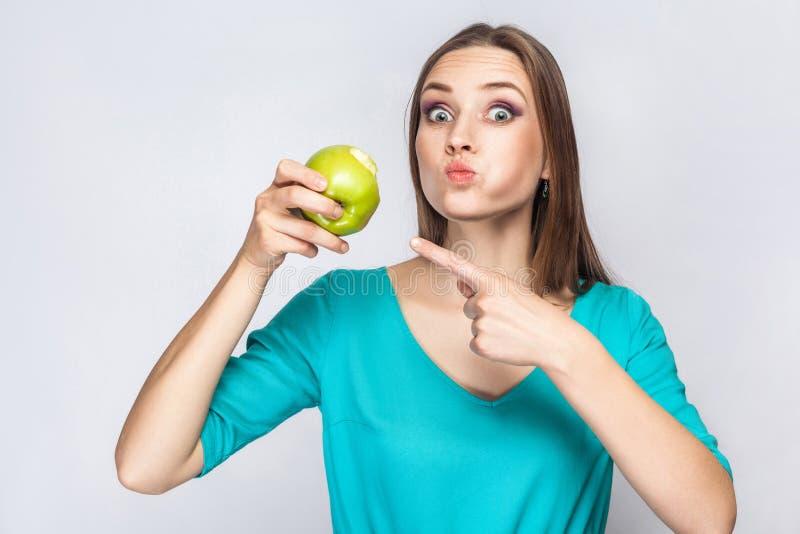 Jonge mooie vrouw met sproeten en groene kledingsholding en het eten van appel en richtend en bekijkend camera met grote ogen royalty-vrije stock afbeelding