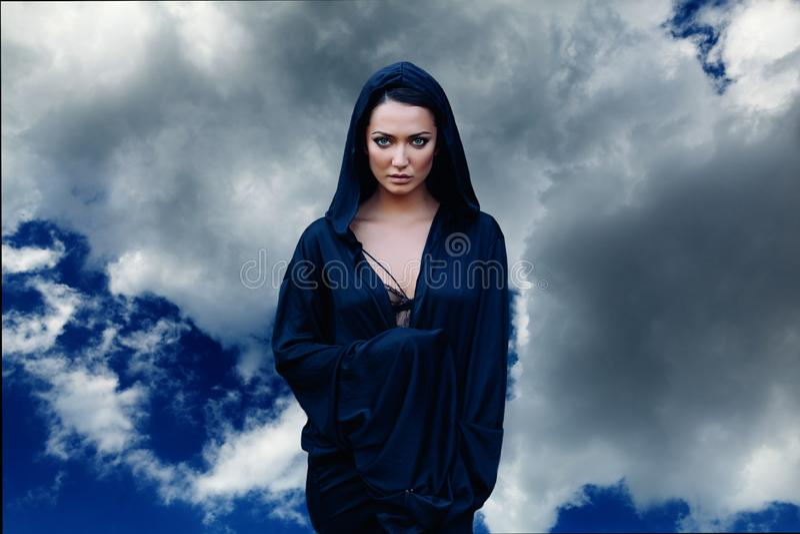 Jonge mooie vrouw met zwart haar en in de donkerblauwe mantel met kap bij de hemelachtergrond stock afbeelding