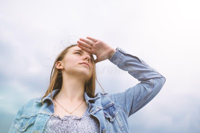 Jonge mooie vrouw op blauwe hemelachtergrond, die ver weg met hand op voorhoofd kijkt Het concept van het onderzoek stock foto's