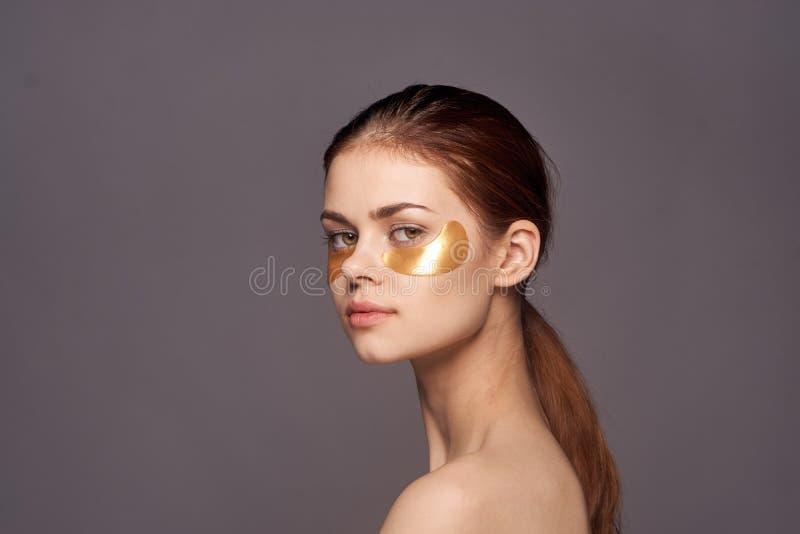 Jonge mooie vrouw op een donkergrijze achtergrond in gouden flarden voor bruidegom, gezichtshuidbehandeling royalty-vrije stock afbeelding