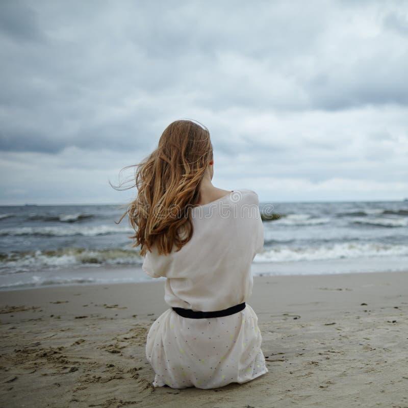Jonge mooie vrouw op koud winderig strand royalty-vrije stock foto's