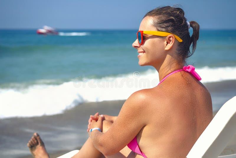 Jonge mooie vrouw op strand De vakantieconcept van de zomer Meisje op lanterfanter tegen blauwe overzees royalty-vrije stock foto