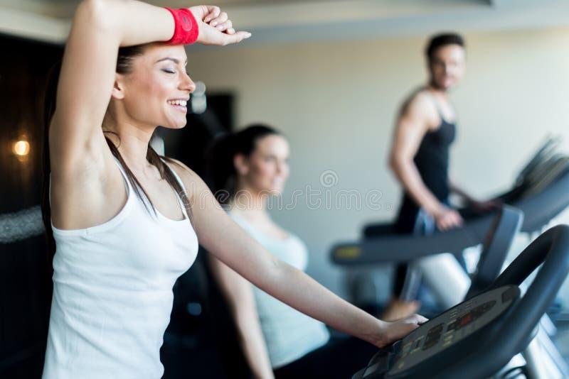 Jonge, mooie vrouw opleiding door een fiets in een gymnastiek te berijden stock foto's