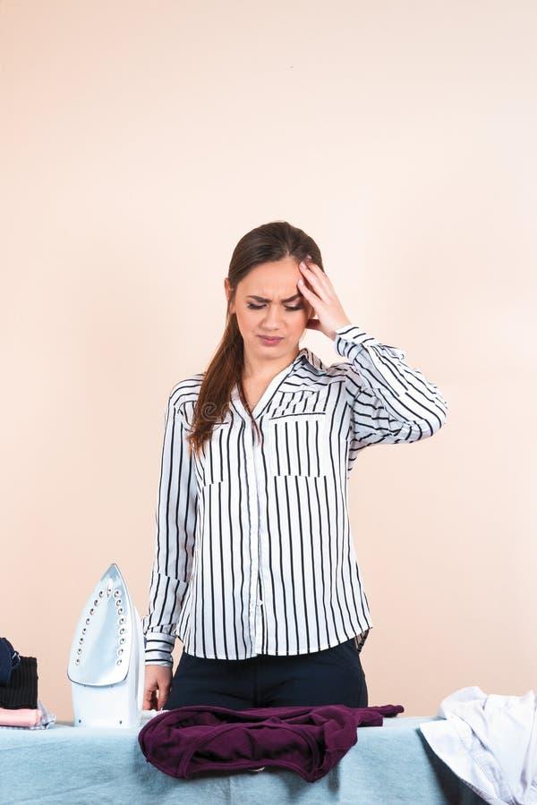 Jonge mooie vrouw in overhemd het strijken, huisvrouwenmoeder die ijzer gebruiken stock foto