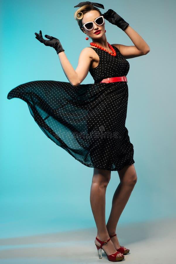 Jonge mooie vrouw in retro speld-omhooggaande stijl met fladderende kleding stock foto's