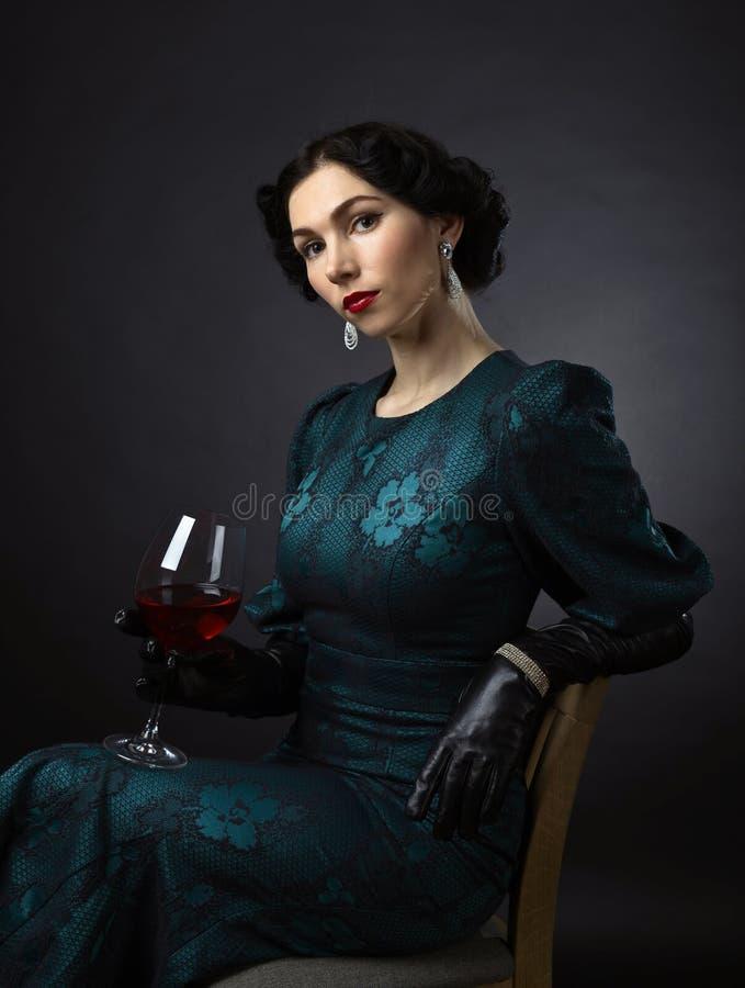 Jonge mooie vrouw in retro stijl met rode wijn stock foto