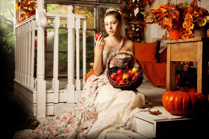 Jonge mooie vrouw in uitstekende kleding op de herfstportiek Schoonheid g stock fotografie