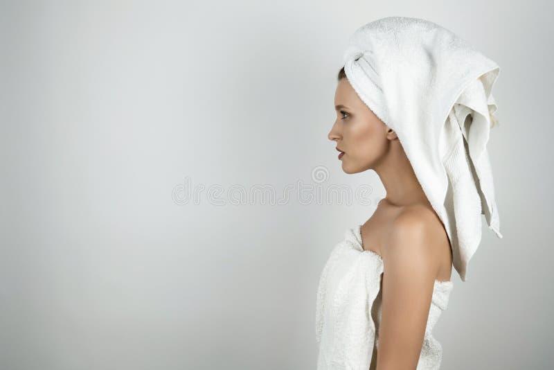 Jonge mooie vrouw in witte handdoek over lichaam en op haar hoofd zich bevindt half geïsoleerde witte achtergrond royalty-vrije stock afbeelding