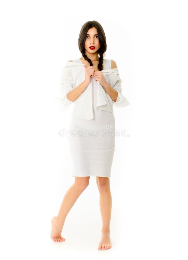 Jonge mooie vrouw in witte kleding op witte achtergrond, Meisje met vlechten het stellen stock afbeeldingen