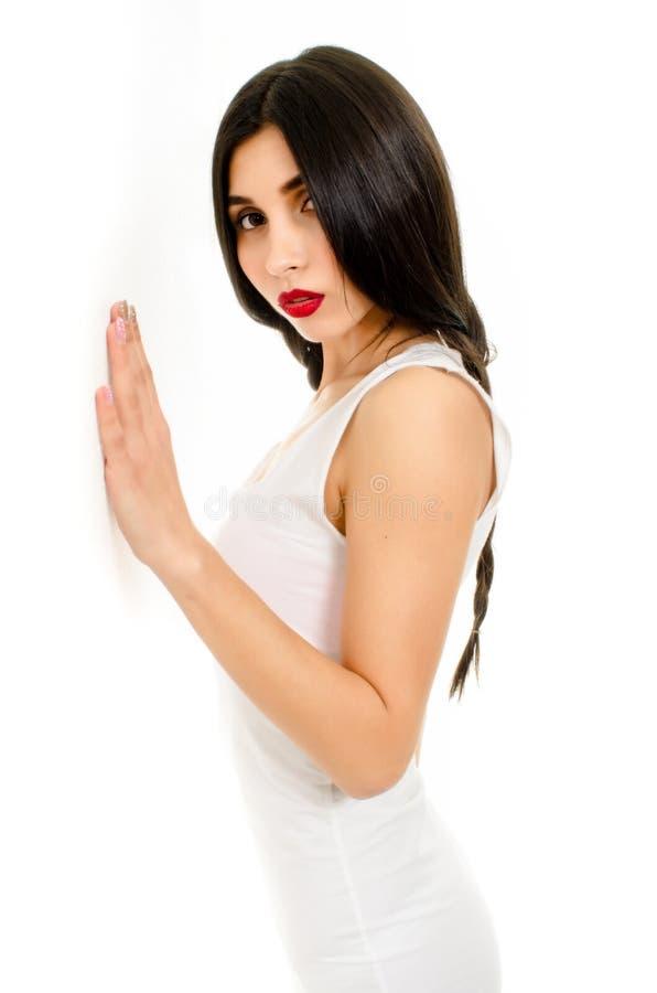 Jonge mooie vrouw in witte kleding op witte achtergrond, Meisje met vlechten het stellen royalty-vrije stock afbeeldingen