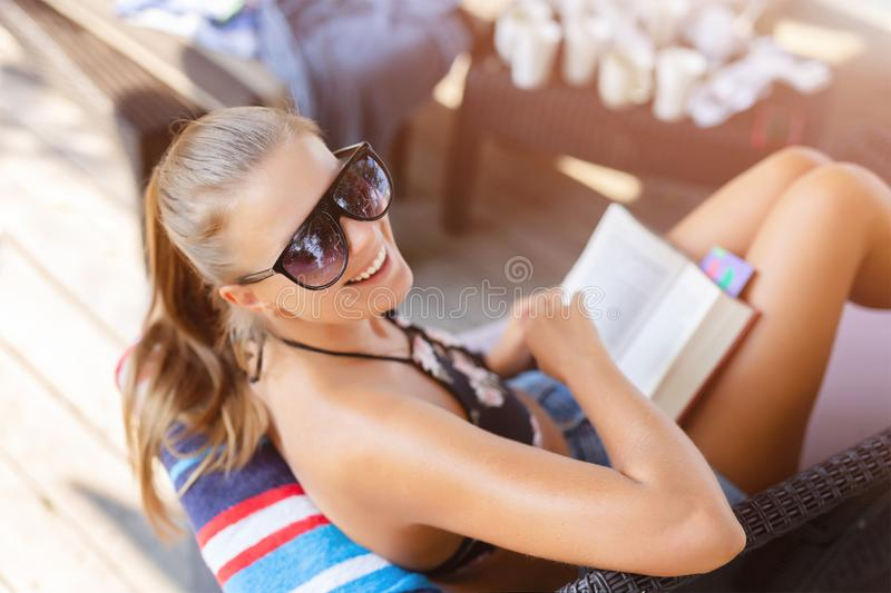 Jonge mooie vrouw in zonnebril die dichtbij strand zitten, en boek hebben glimlachen lezen tijdens de zomervakantie stock afbeeldingen