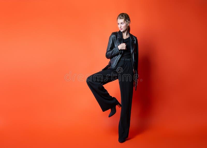 jonge mooie vrouw in zwarte kleren die in de Studio stellen Aantrekkelijk vrouwelijk model in modieuze vrijetijdskleding royalty-vrije stock fotografie