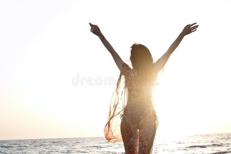 Jonge mooie vrouw in zwempak die zich op het strand bevinden stock foto's