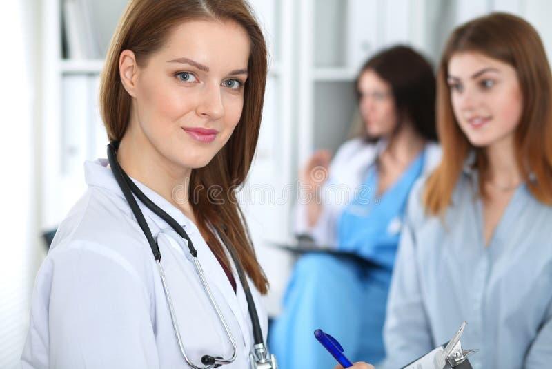 Jonge mooie vrouwelijke arts die terwijl het raadplegen van haar patiënt glimlachen Arts op het werk Geneeskunde en gezondheidszo stock foto