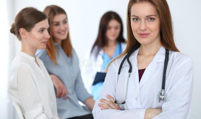 Jonge mooie vrouwelijke arts die terwijl het raadplegen van haar patiënt glimlachen Arts op het werk Geneeskunde en gezondheidszo stock afbeeldingen