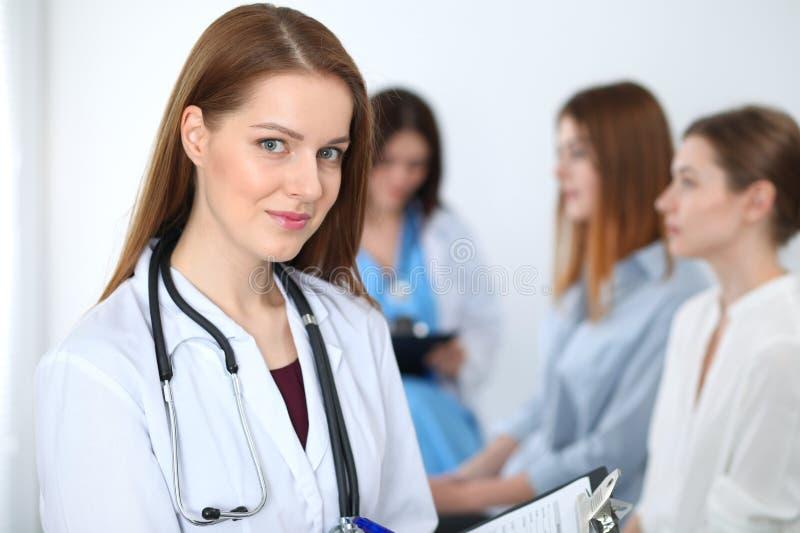 Jonge mooie vrouwelijke arts die terwijl het raadplegen van haar patiënt glimlachen Arts op het werk Geneeskunde en gezondheidszo royalty-vrije stock foto