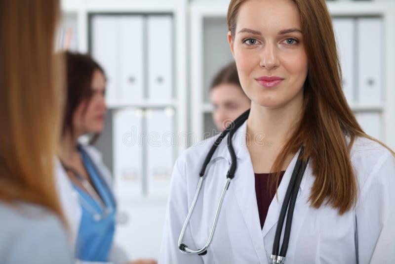 Jonge mooie vrouwelijke arts die terwijl het raadplegen van haar patiënt glimlachen Arts op het werk Geneeskunde en gezondheidszo stock afbeelding