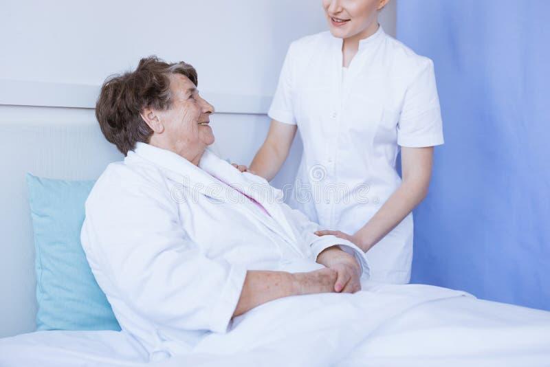 Jonge mooie vrouwelijke arts en hogere pati?nt bij het ziekenhuis royalty-vrije stock afbeeldingen