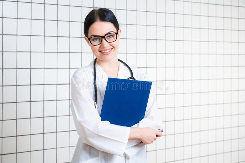 Jonge mooie vrouwelijke arts in witte chirurgische laag met zwarte stethoscoop en blauwe document houder in handen die bevinden z royalty-vrije stock afbeeldingen