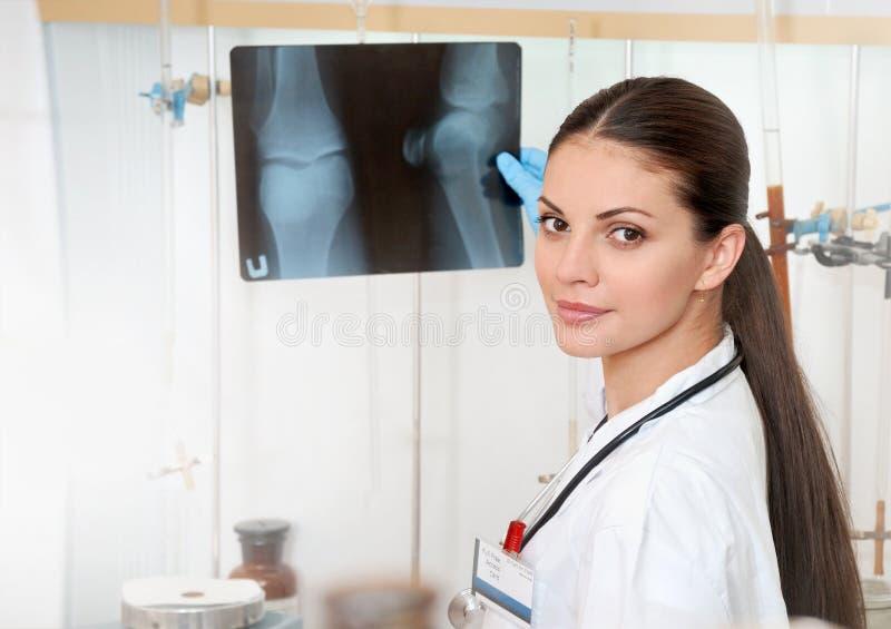 Jonge mooie vrouwelijke arts in witte laag met röntgen in handen stock foto's