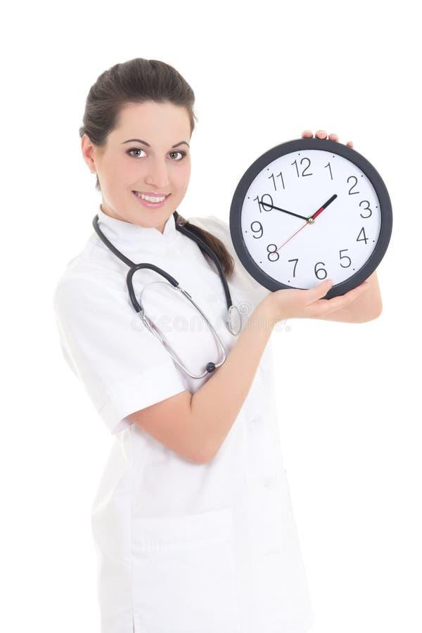 Jonge mooie vrouwelijke die arts met klok op wit wordt geïsoleerd stock foto's