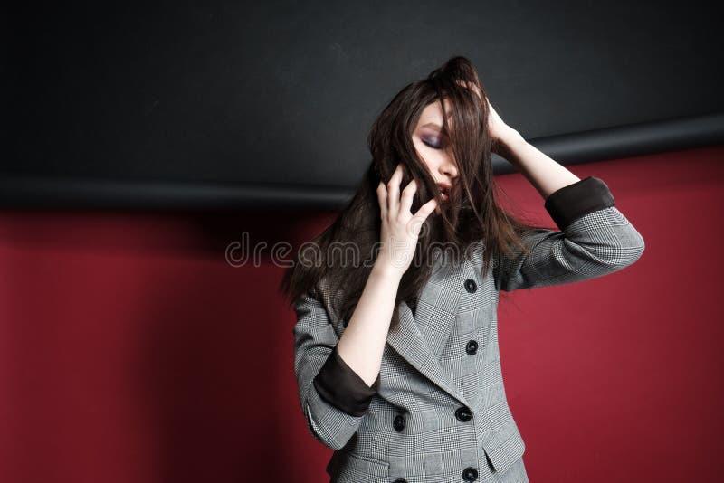 Jonge mooie vrouwelijke mannequin in een bedrijfs modieus kostuum op een rode en zwarte achtergrond royalty-vrije stock foto
