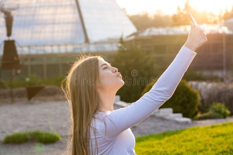 Jonge mooie vrouwelijke student die een eend-gezicht zelf in de pa nemen stock afbeelding